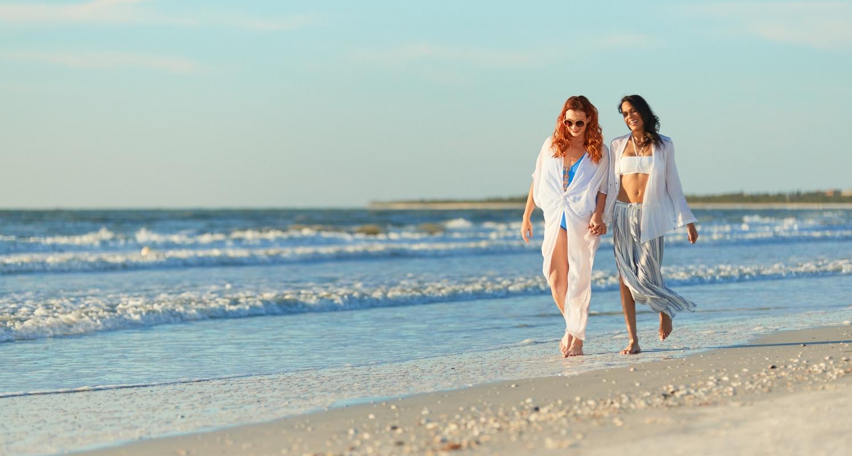 LGBT couple enjoying a walk on the beach