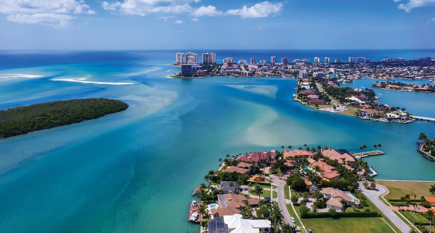 An aerial view of Marco Island, Florida shows calm blue Gulf waters, resorts and mansions lining the shore, white sand, palm trees and a mangrove island.