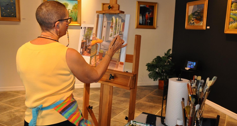 Artist Inez Hudson at work in her studio/gallery at the Esplanade.  Photo courtesy Naples Marco Island Everglades CVB