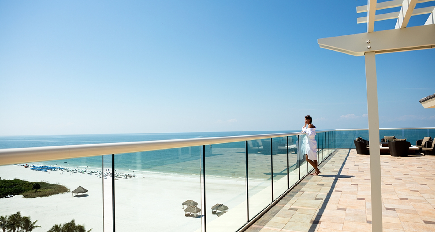 A woman stands on a balcony overlooking a sunny beach.