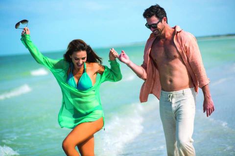 A couple takes a romantic stroll on a beach in the Naples and Marco Island area of Florida.