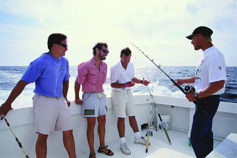 A fishing guide gives pointers during a fishing charter.