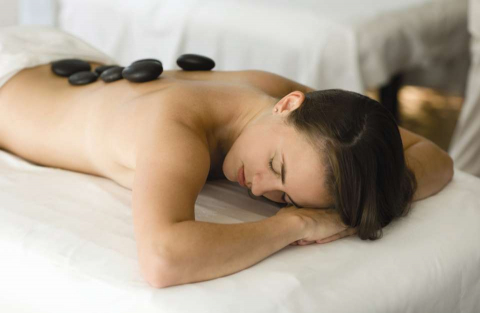 A woman enjoys a hot stone massage at a hotel spa in Naples, Florida.