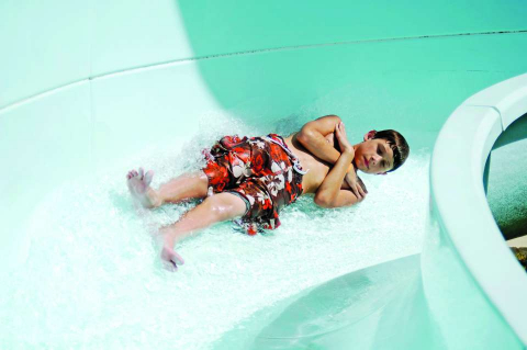 A child zips down a water slide at Sun-N-Fun Lagoon water park in Naples, Florida.