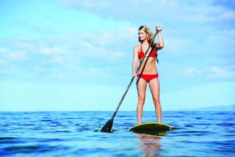 A woman stands atop a stand-up paddleboard.