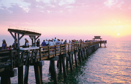 A crowd gathers on the Naples Pier at sunset.