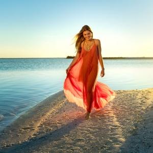 A Young Woman Walks along the Paradise Coast