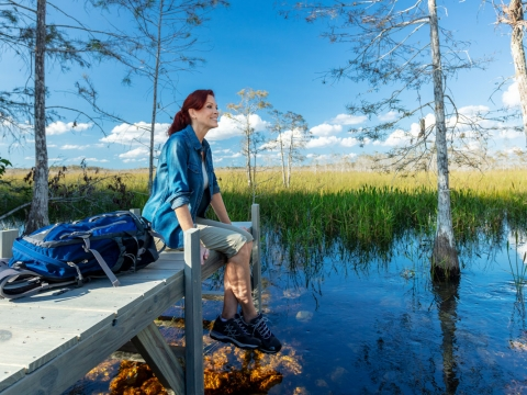 A woman sits on a dock during a hike in the Everglades